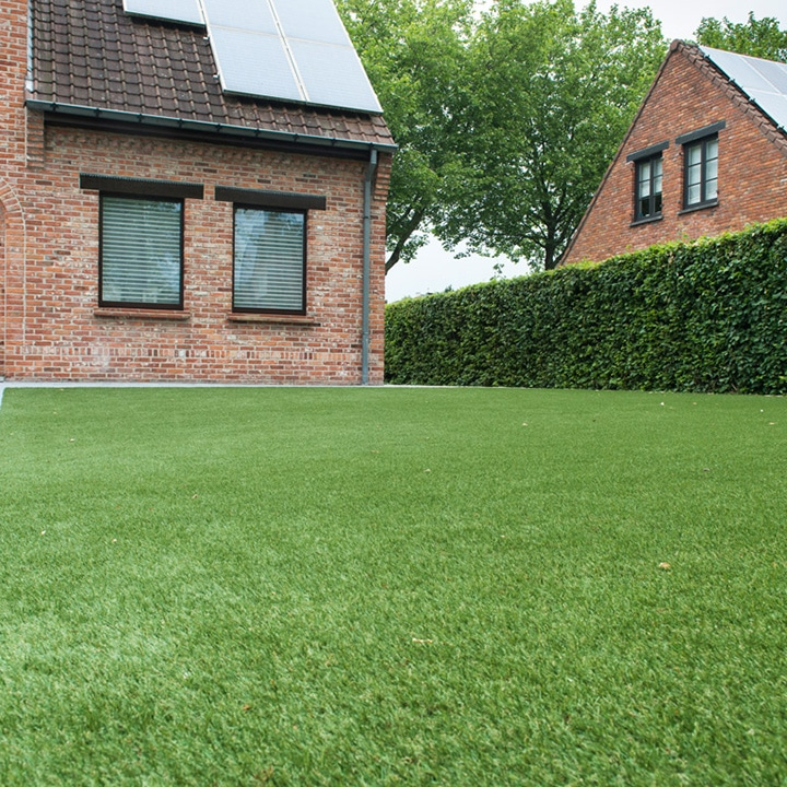 Exbury artificial grass laid in garden of contemporary property. Mature hedges